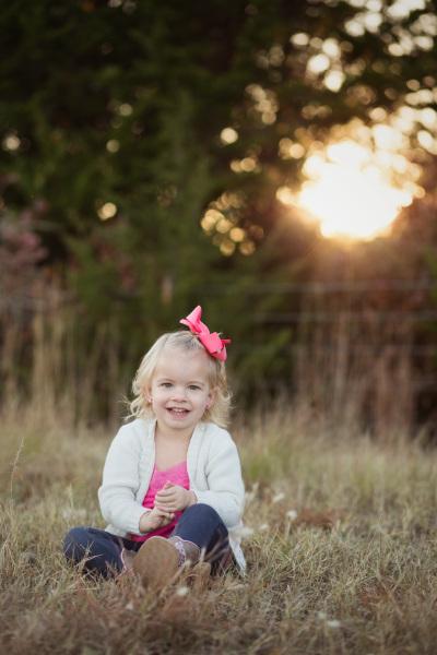 little girl wearing pink bow sitting in field in stillwater oklahoma