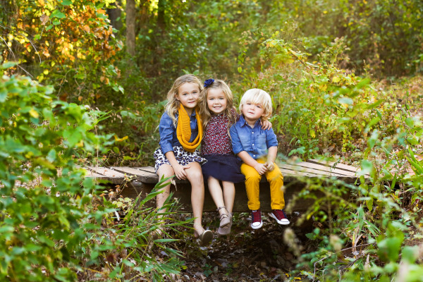 three sibling sitting on wood bridge at fink park in edmond oklahoma