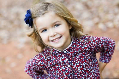little girl wearing blue bow looking at camera at fink park in edmond oklahoma