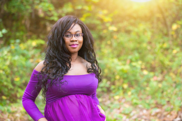 woman wearing purple maternity dress looking at camera in edmond oklahoma