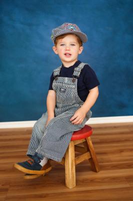 little boy sitting on red stool wearing thomas the train hat in edmond oklahoma