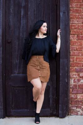 senior girl wearing black standing against wood door in bricktown oklahoma city oklahoma