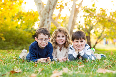 three siblings laying on grass looking at camera at will rogers park in oklahoma city oklahoma