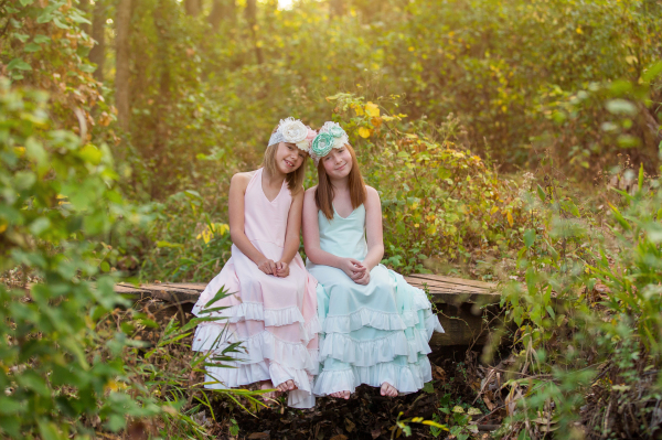 little girls wearing dresses and hair bows sitting on wood bridge in edmond oklahoma