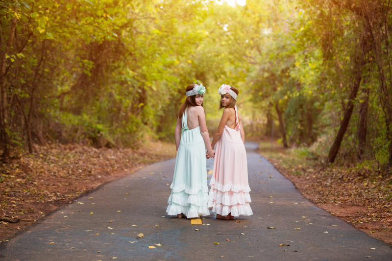 little girls wearing dresses and hair bows holding hands while walking on trail in edmond oklahoma