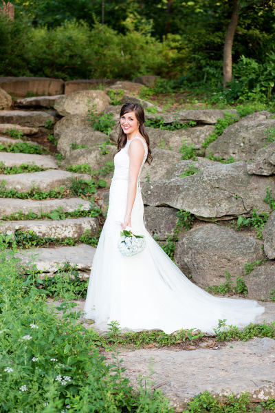 bride standing on rock staircase holding flowers in tulsa oklahoma