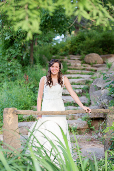 bride leaning on wood rail in park in tulsa oklahoma