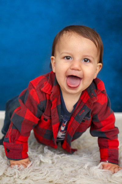 little boy wearing black and red shirt with blue background at studio in edmond oklahoma