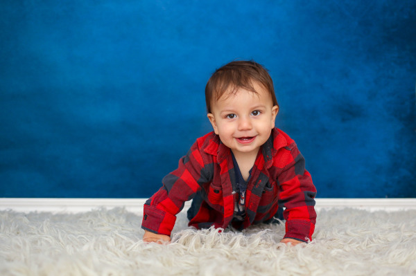 little boy wearing black and red shirt with blue crawling to camera background at studio in edmond oklahoma