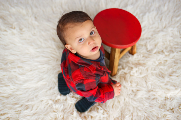 little boy wearing red and black shirt sitting on white rug in edmond oklahoma