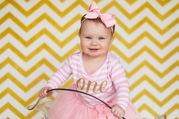 little girl with pink first birthday outfit and big pink bow in studio oklahoma city photographer