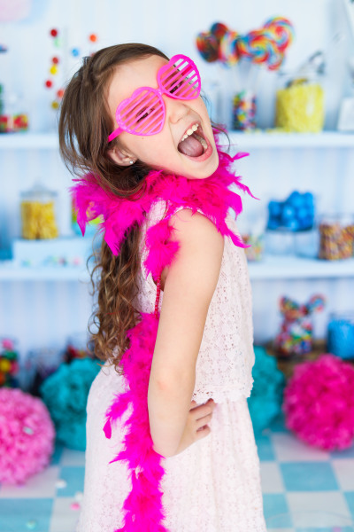 little girl with candy shop background wearing pink heart glasses and pink boa oklahoma city photographer