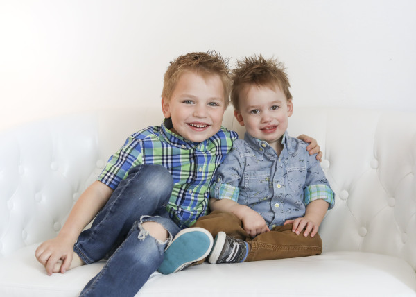 little brothers sitting on white couch in studio oklahoma city photographer