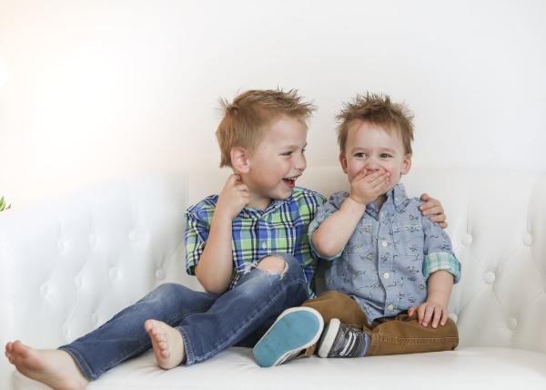 little brothers sitting and laughing on white couch in studio oklahoma city photographer