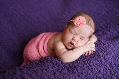 newborn baby girl with pink wrap and bow laying on purple blanket oklahoma city photographer