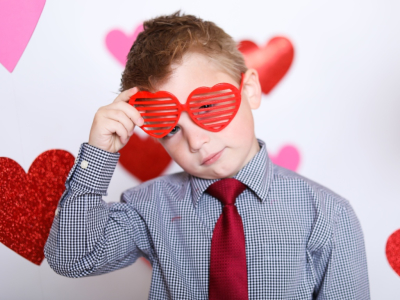 Little boy wearing red heart shaped glasses