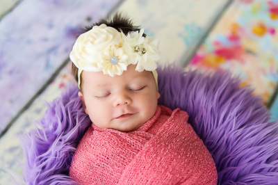 Newborn girl wrapped in pink with big white bow