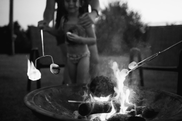 black and white image of children roasting marshmallows over a camp fire