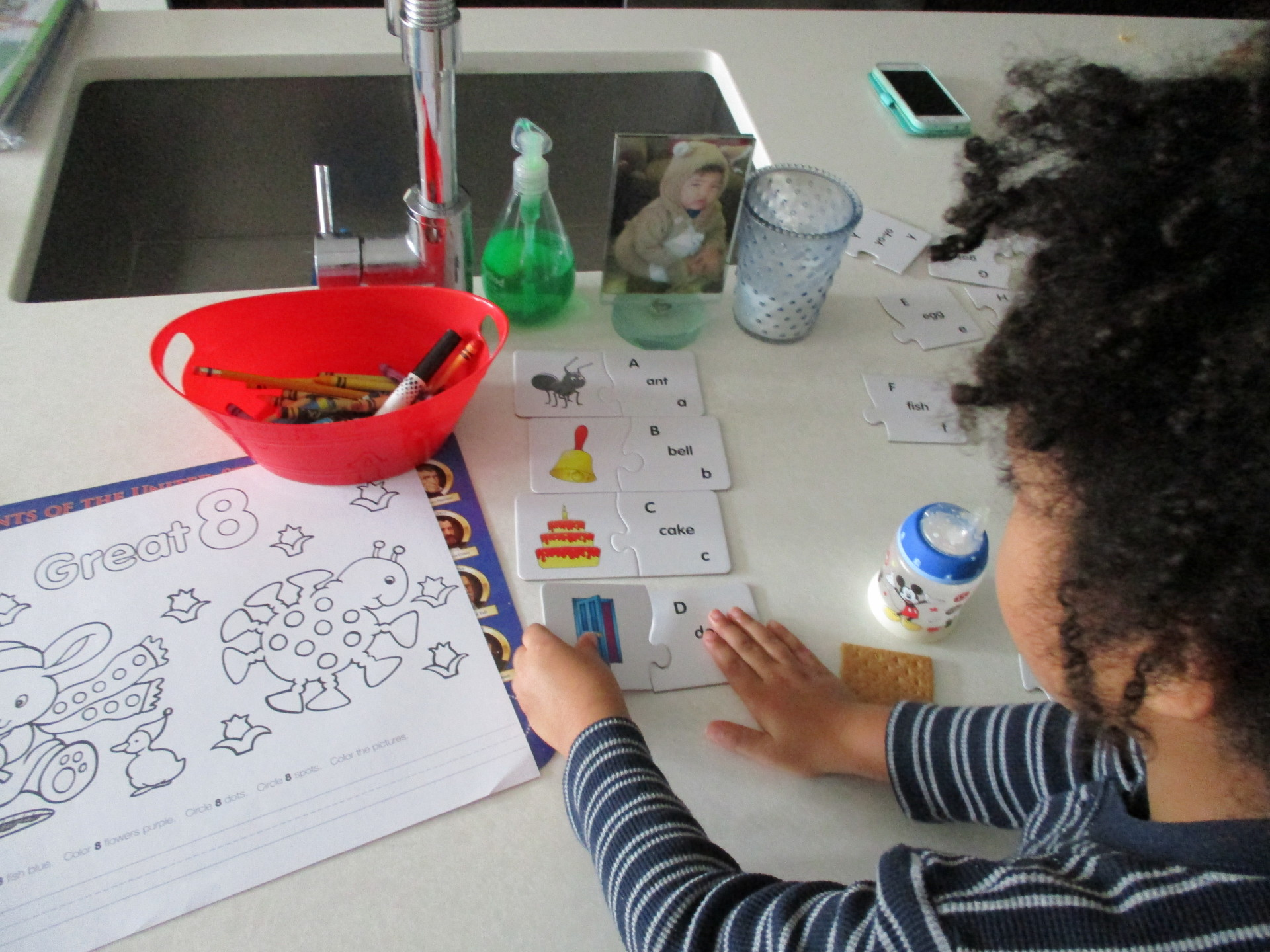 Isaiah working on alphabet puzzle