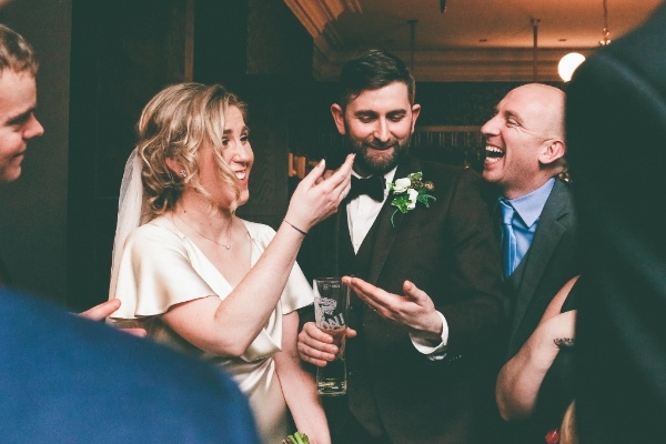 A couple in love on their wedding day being amazed by the magic of Danny Jewell in Manchester during the drinks reception