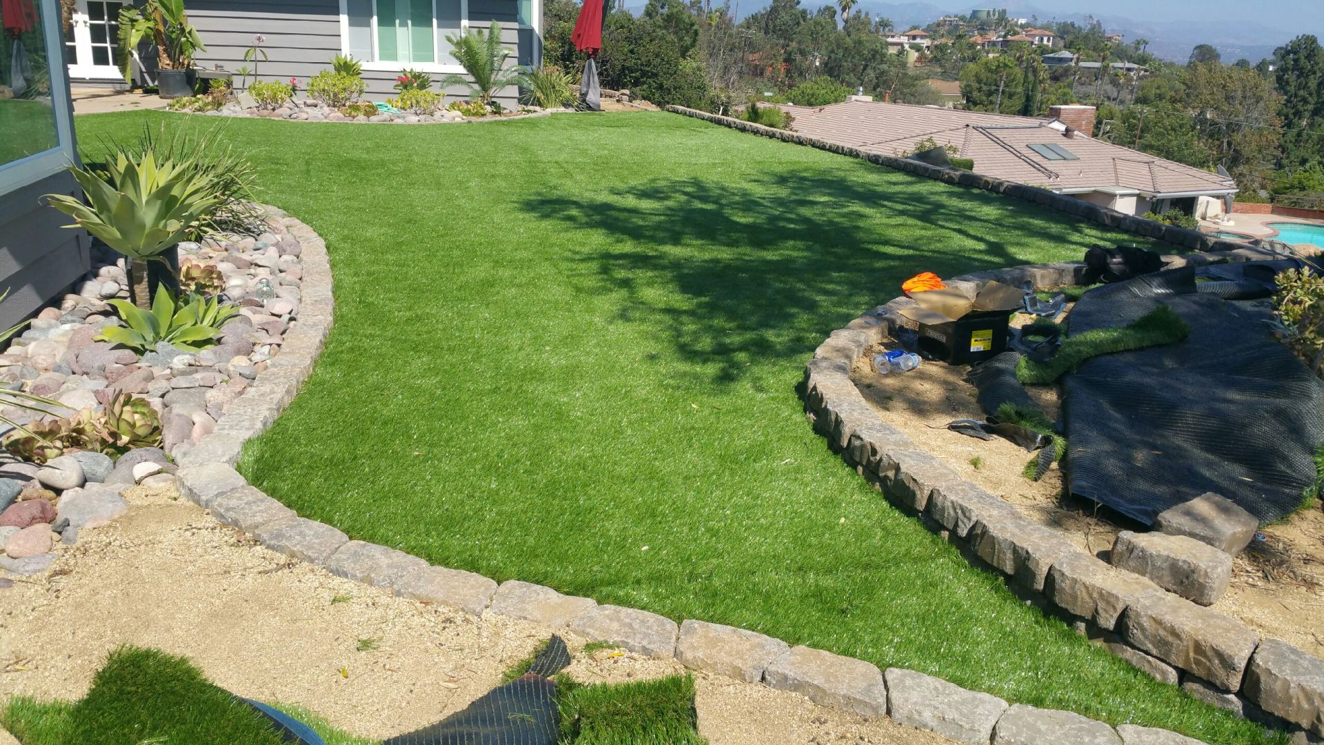 Grass with mow strip and a few plants with pebbles