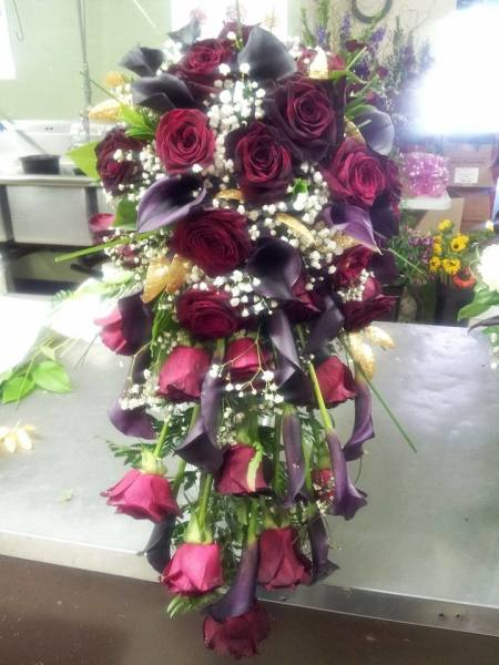 Cascade of black bacara roses, burgundy mini calla lilies,
