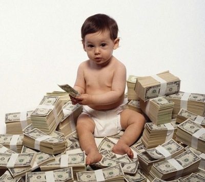 toddler child sitting on large pile of money