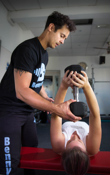 Instructing the dumbbell pullover with a client, handing over the dumbbell
