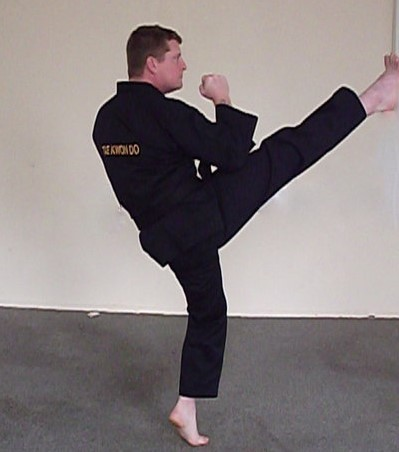 Image of the TKD martial arts instructor making a front high section kick uttilising the ball of foot at head hight.