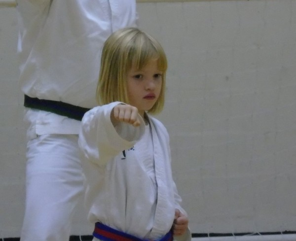 Image of a young female student mid practice of a taekwondo movement, the student trains a martial art class in sutton coldfield
