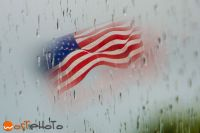 American flag waving in the wind, seen from behind a window with rain drops on it