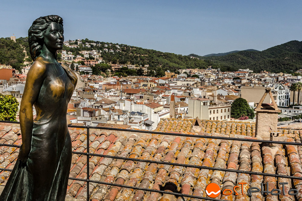 Bronze statue of Ava Gardner looking at panorama of Tossa de Mar, Catalonia, Spain