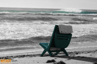 Empty green beach chair at the beach facing the ocean in Palm Beach, Florida