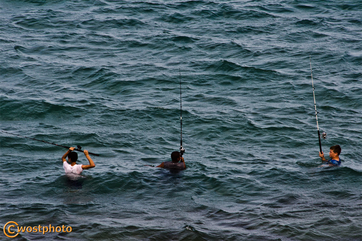 Three boys fishing while standing in the ocean water in Palm Beach, Florida, USA