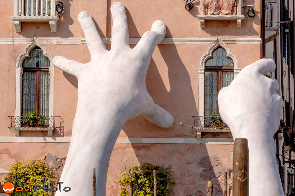 Huge hands coming out of the canal water supporting the Venetian hotel in Venice/Italy