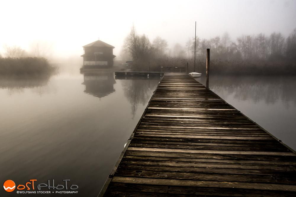 Wooden landing stage at the foggy Wallersee in Seekirchen/Austria