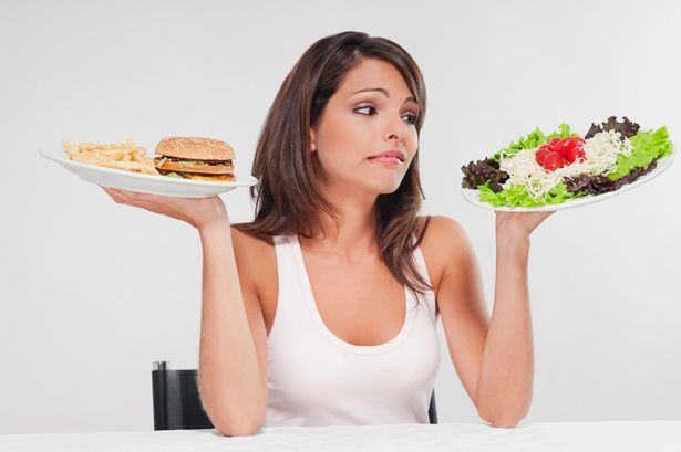 picture of a girl contemplating on which plate of food she should eat