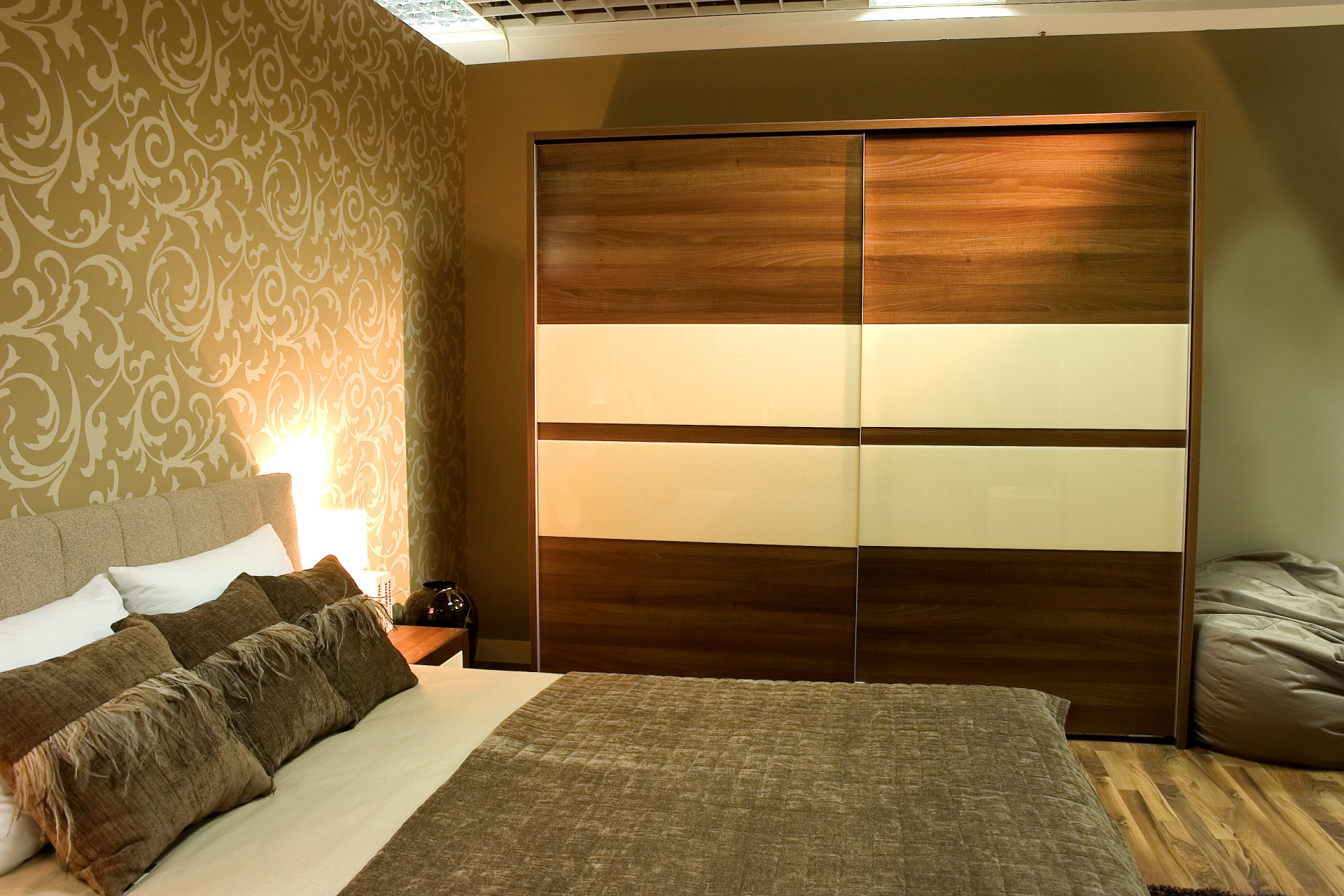 Modern bedroom with brown sliding wardrobe and bed with two pillows. Landsons.co.uk