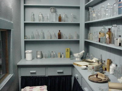 The pharmacy in Fr. Ravalli's cabin shows shelves full of antique medicine bottles.