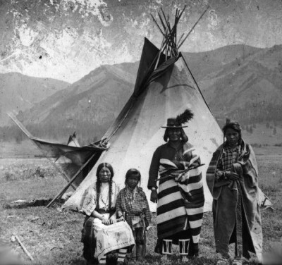 A Salish family outside of a lodge