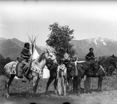 Salish shown in traditional dress on horseback.