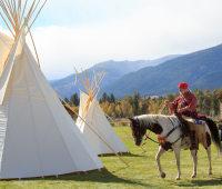 Mountain man on horseback riding past tipis
