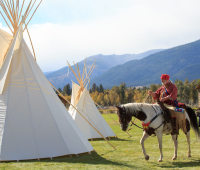 Mountain man on horseback riding past tipis
