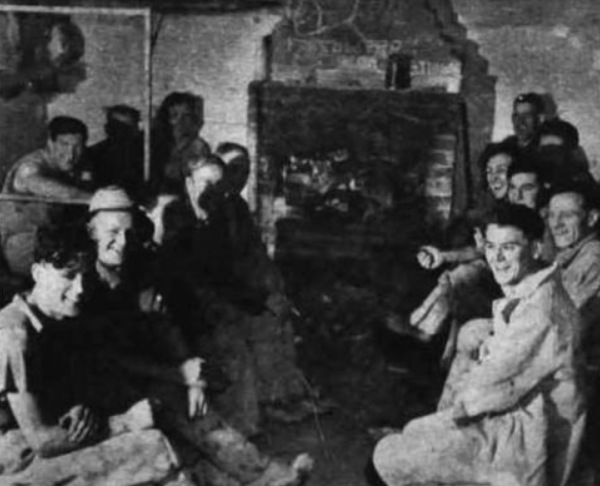 """Around the fire in the crew's """"glory hole,"""" smiling over a shift ended - and a job well done in spite of Arctic cold and ice-hard rock."""