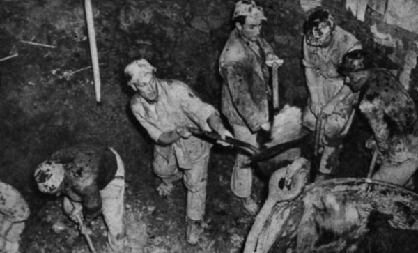 """Mucking out"" at the shaft floor - more of the crew : Left to right, Lawson, Bert Holehouse, Eddie Gilfilian, Chantry and Chambers, fill the ever-hungry ""hoppit""."