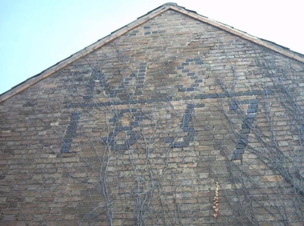 Inscription on the side of 221 Main Street (Matthew Shepherd 1857)