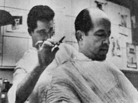 Getting a haircut. Phil Silvers hasn't any favorite barber -- just any one who's near