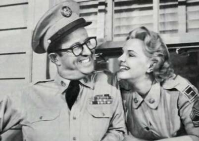 Bilko gives a big smile to his love interest in The Phil Silvers Show, and gets one back just as big and just as enigmatic. She's WAC Sergeant Hogan, the commanding officer's secretary -- in real life, actress Elisabeth Fraser