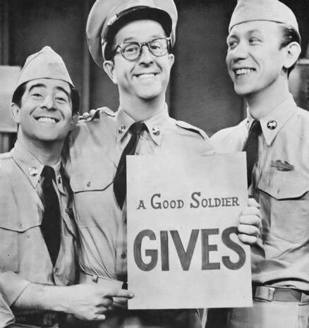 Phil holds his favorite sign. Harvey Lembeck points to the sign as Allan Melvin watches