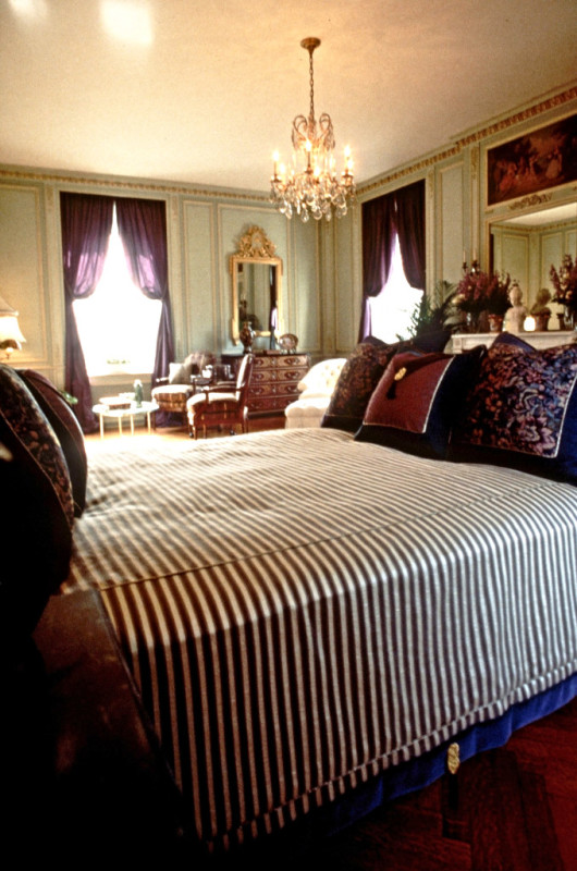 Photo of a mansion master bedroom showing custom bed covering and toss pillows in the foreground, plus seating areas in a Louis XVI room. Interior design done by Steven C. Adamko, owner and founder of Spectrum Interiors in Kalamazoo Michigan
